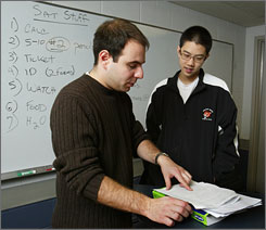 Arthur Su, of Newton, Mass., right, gets some advice on the writing section of the SAT from teacher Cary Wagner in March 2006.