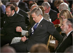 President Bush holds hands and prays with guests during the National Day of Prayer event in the White House's East Room.