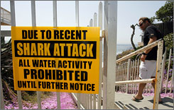 Sam Lunde walks past a sign prohibiting water activity above Tide Beach after a shark attack in Solana Beach, Calif.