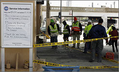 A sign displays transit service information next to construction workers at a Chicago Transit Authority Red Line station in Chinatown.
