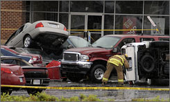 A firefighter checks inside cars stacked on top of one another following an apparent afternoon tornado April 28 in Colonial Heights, Va.