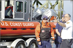 Biddeford Fire Chief Robert Fournier, right, consults with Coast Guard personnel before looking for a lost kayaker May 9. The body of Tim Gutmann was found that day.