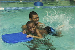 USA Swimmer Cullen Jones helps Tavion Traynham with the kick board while giving swim lessons to six 8-year-olds at the Butler-Gast YMCA in Omaha. Jones' lesson is part of USA Swimming's Make A Splash program.