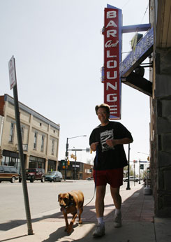 Jeff Wheeler of Brighton and his dog Buddy jog past Jordinelli's Bar, which opened in 1934 in the city's downtown area.