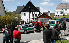 Police officers and members of the media on Monday surround a house in Wenden, Germany, where police say three dead babies were found in a freezer. The babies' mother has been arrested, police say.