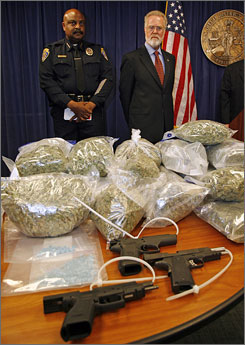 San Diego State University president Stephen Weber, right, and SDSU chief of police John Browning, left, stand over a guns and drugs seized during the arrest of 96 people on drug charges May 6.