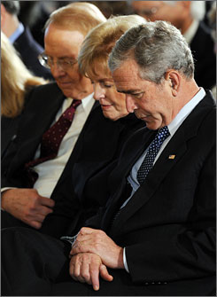 "Focus on the Family founder James Dobson, left, wife Shirley, and President Bush pray together on May 1. Dobson, who endorsed former-pastor Mike Huckabee for president, has not signed on to a manifesto reclaiming ""evangelical"" from politics."