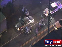 This image from television shows police officers kicking and beating suspects they have pulled from a car during a traffic stop in Philadelphia on Monday. The scene was captured by a WTXF-TV television helicopter.