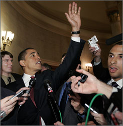 Sen. Barack Obama waves to tourists Thursday as he is followed by members of the news media through the U.S. Capitol.