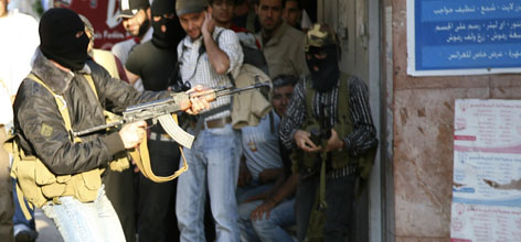 Shiite opposition gunmen shoot with rifles during clashes in a street in Beirut, Thursday. The clashes followed a defiant speech by Hezbollah leader Hassan Nasrallah, who warned his Iranian-backed militant group would respond with force to any attacks.