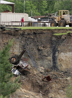 A truck falls into a giant sinkhole as a tractor is used to remove other equipment from the site May 7 in Daisetta, Texas.