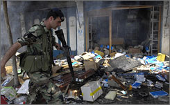 A Lebanese soldier walks in front of a burnt out shop, which was set alight in the violence that broke following a shooting at a funeral in Beirut.