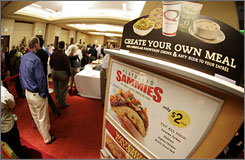 "Attendees line up to sample the new fare available at Quiznos at the company's annual meeting in Denver last December. Quiznos has sold 5 million of its $2 mini ""Sammies"" sandwiches since their November introduction. The 200- and 300-calorie sandwiches are now 16 percent of sales."