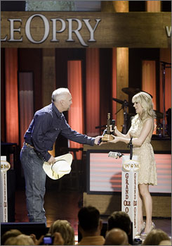 Carrie Underwood is inducted as the newest member of the Grand Ole Opry by fellow Opry member Garth Brooks  Saturday in Nashville.