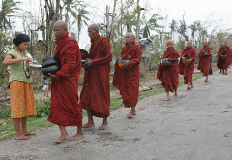 Monks accept food handouts on Tuesday in Kundangon, Burma, in the wake of a devastating cyclone that ravaged the Asian country.