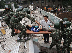 Soldiers cart the wounded out of the rubble in Sichuan Province, China, on Tuesday after the deadly earthquake that rocked China the day before.