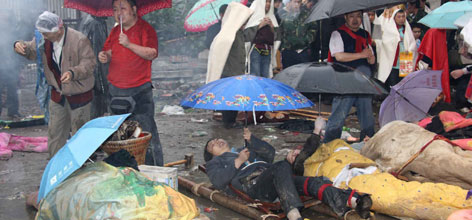 Locals wait to be transported to safe areas as the injured lay in the open air as rain falls May 13 in Sichuan's Beichuan County.
