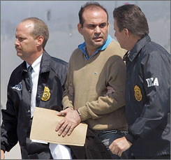 Colombian paramilitary Salvatore Mancuso, center, is escorted by U.S. DEA agents at his arrival in Opa-locka, Fla. May 13.
