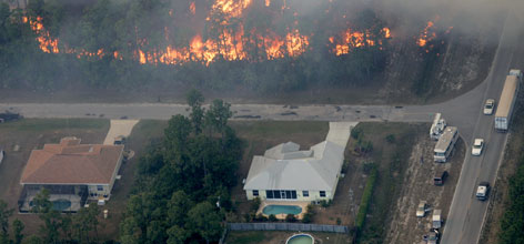 Flames approach a house as wildfires burned hundreds of acres of a residential community in Palm Bay, Fla. Wildfires continued to burn for the third day in Brevard County, in east Central Florida.