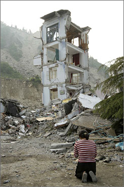 A relative of an earthquake victim prays for the dead at the site of a collapsed school building in Wenchuan, Sichuan province, Thursday.