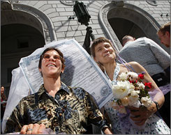 Alice Heimsoth, left, and Christmas Leubrie carry a large copy of their 2004 marriage certificate Thursday.