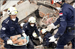 Members of a rescue team from Singapore search for survivors in the rubble of a bank in Shifang City, China. Rescuers have shifted their efforts to clearing out dead bodies instead of trying to find survivors.
