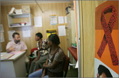 Patients sit in the waiting room of an AIDS/HIV clinic in Winterton, South Africa, in March. At left is Bernhard Gaede, who heads the clinic.