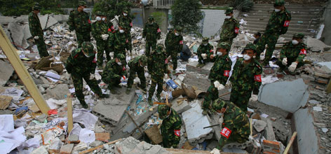 China soldiers search for survivors at a collapsed school in Sichuan province, China, Tuesday. The nation's worst earthquake in 58 years jolted the region on May 12, leaving more than 40,000 dead.