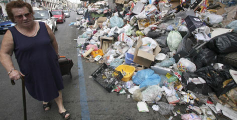 A woman walks past piles of trash piled on a sidewalk in Naples on May 17. A resurgent trash crisis in Naples and squabbling over immigration pose challenges to newly-elected Prime Minister Silvio Berlusconi.
