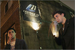 Ali Elgayar, left, and Beau Hall smoke together outside a bar in Hoboken, N.J., in 2007. If you're a smoker and you quit, you might motivate a friend of a friend of a friend to quit, researchers suggest.