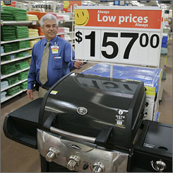 Store manager Dane Bryan shows a barbeque grill on sale at a Wal-Mart store in West Chester, Ohio. One in three Americans will spend their vacations at home this summer because of tightening budgets and higher gas prices. Wal- Mart is among those trying to cash in by doing a big push on items like gazebos and barbeque equipment.