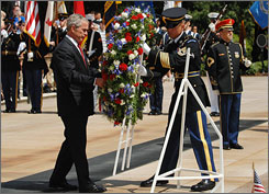 President Bush is helped by a member of a military honor guard as he places a wreath at the Tomb of the Unknowns during Memorial Day ceremonies Monday at Arlington National Cemetery in Arlington, Va.