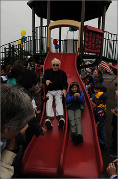 Kirk Douglas, 91, christens the new sliding board at Beethoven Elementary School in Los Angeles by taking the first slide with student Celeste Segura, 10 of Los Angeles.