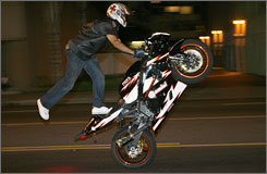 "A ""stunter"" rides down Santa Monica Boulevard in L.A. Police read stunters? websites to find out where they?ll meet."