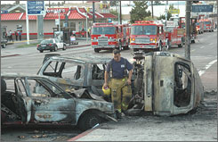 A firefighter examines the shells of vehicles that were involved in a chain-reaction crash Monday night in South Los Angeles that killed five people, including two children.