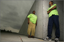 Pam Dashiell, left, and Charles Allen of the Holy Cross Neighborhood Association stand in front of the levee wall built in the Lower 9th Ward after Hurricane Katrina in 2005.