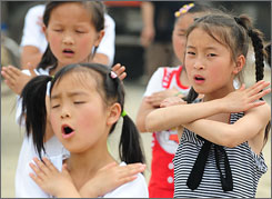 Young quake survivors sing during performance therapy for children at a camp for the displaced and homeless in Mianzhu in southwest China's quake-stricken Sichuan province.