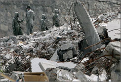 Soldiers with protective suits gather near the rubble of a building collapsed by May 12 earthquake in Sichuan Province of China, Wednesday.