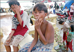 Cambodian boys sit along the banks of the Tonle-Sap river smoking cigarettes in Phnom Penh, Kampuchea in August 1995.