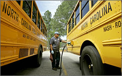 Robbie Sutton, a school employee, fills a bus with diesel fuel at Southern Nash High School in Bailey, N.C., Thursday. Every three and a half school days, Nash-Rocky Mount School buses consume 7,500 gallons of fuel.
