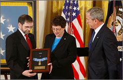 President Bush hands the Medal of Honor to Thomas and Romayne McGinnis, parents of late Army soldier Ross Andrew McGinnis, during a ceremony in the East Room at the White House on Monday. McGinnis, 19, from Knox, Pennsylvania, was killed Dec. 4, 2006 when he jumped on a grenade to save other troops in Iraq.