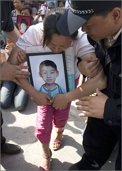 Chinese police officers take away one parent who lost a child in the May 12 quake outside the court house in China's Sichuan province, Tuesday.
