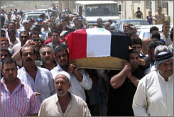 Mourners carry a flag draped coffin of a police officer who was killed by gunmen during a funeral in Kut, southeast of Baghdad, Wednesday.