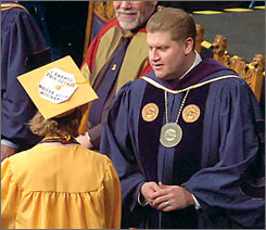 """A graduate wearing a mortarboard that reads """"I earned this degree"""" and """"Garrison must resign"""" refuses to shake West Virginia University President Mike Garrison's hand during the Honors Convocation in May. Garrison decided to resign today amid growing tensions over a degree scandal involving the governor's daughter."""