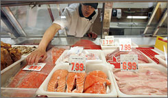 Jerry Velasco places prices on seafood at Save More Meats in Pacifica, Calif.