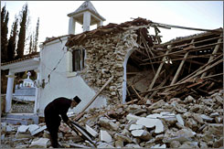 Seimologists warn aftershocks from Sunday's powerful earthquake in Greece might be coming. Here, a priest picks through rubble on Sunday in the village of Valmi, in Ileia prefecture.