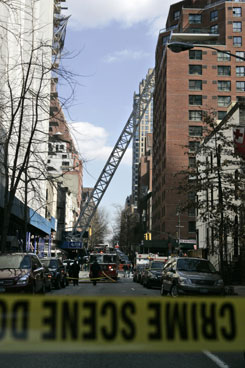 A crane leans between two buildings on March 15 after its collapse on 51st Street in New York killed seven.