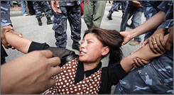 A woman is held by police during a protest by Tibetan exiles in front of the Chinese Embasssy visa section in Katmandu, Nepal, on Tuesday.