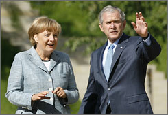 President Bush walks with German Chancellor Angela Merkel at a government guest house in Meseberg, Germany, on Wednesday. During a press conference with Merkel, Bush said he has not ruled out using military force against Iran in a standoff over nuclear weapons.