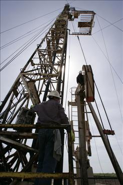 Oil rig workers put a rod into a well in the Permian Basin oil fields, in Midland, Texas.